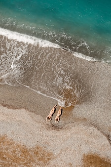 Luchtfoto van een vrouw in de middellandse zee in turkije. mooie zomerse landschap met een meisje, helder azuurblauw water, golven en zandstrand op een zonnige dag. bovenaanzicht van een vliegende drone.