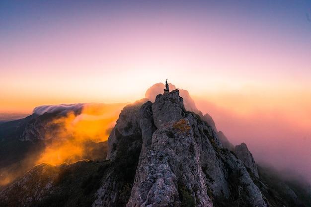 Luchtfoto van een vrouw met handen omhoog op de top van de berg bij zonsondergang