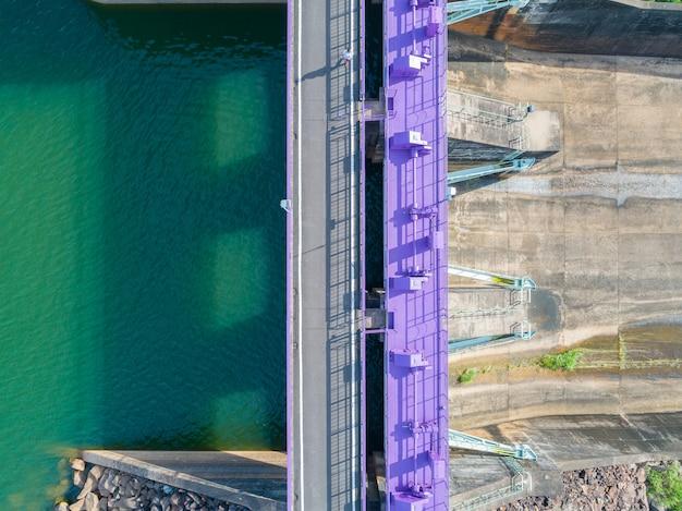 Luchtfoto van een waterkrachtcentrale en dam, topview hydraulische slagboomdeur - betonnen waterkering stroomafwaarts helling.