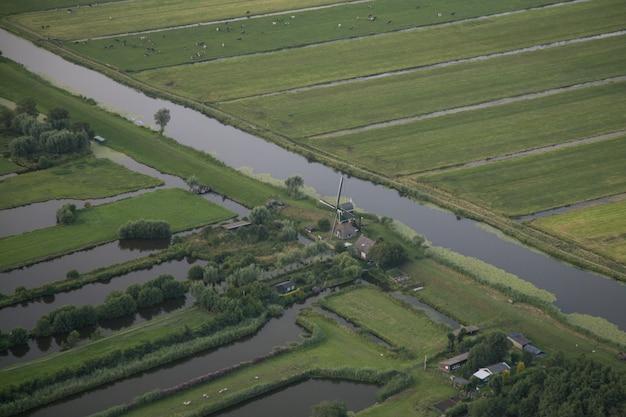 Luchtfoto van een waterstroom midden tussen grasvelden bij nederlandse polder