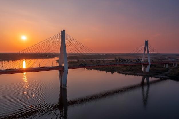 Luchtfoto van een witte hangbrug met twee enorme pilaren boven een rivier bij zonsopgang