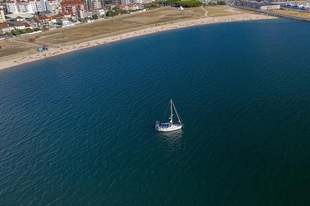 Luchtfoto van een witte zeilboot voor het zandstrand van een stad met mensen die ontspannen