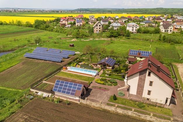 Luchtfoto van een woonhuis in de zomer met blauwe zonne-fotovoltaïsche panelen op het dak en in de tuin.