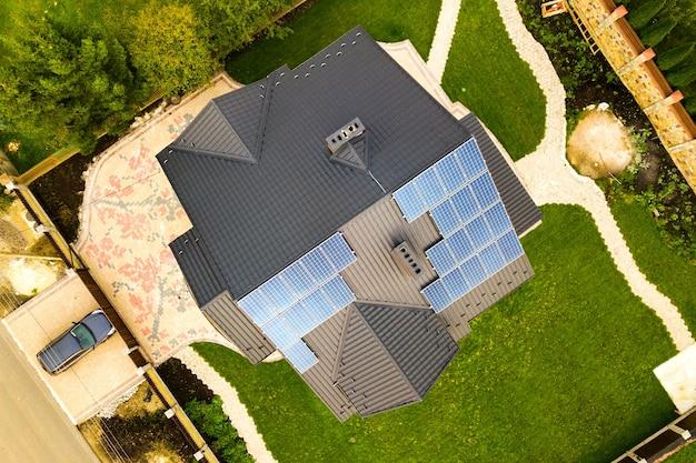 Luchtfoto van een woonhuis met fotovoltaïsche zonnepanelen voor het produceren van schone elektriciteit op het dak. autonoom huisconcept.