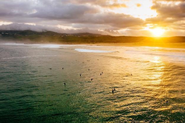 Luchtfoto van een zonnige kust met veel mensen die in het water zwemmen