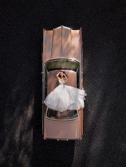 Luchtfoto van elegante bruid liggend op het dak van een roze retro auto