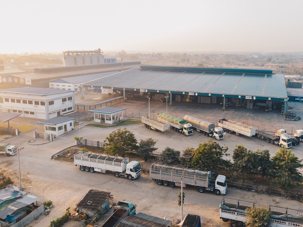 Luchtfoto van fabrieksvrachtwagens geparkeerd in de buurt van het magazijn overdag