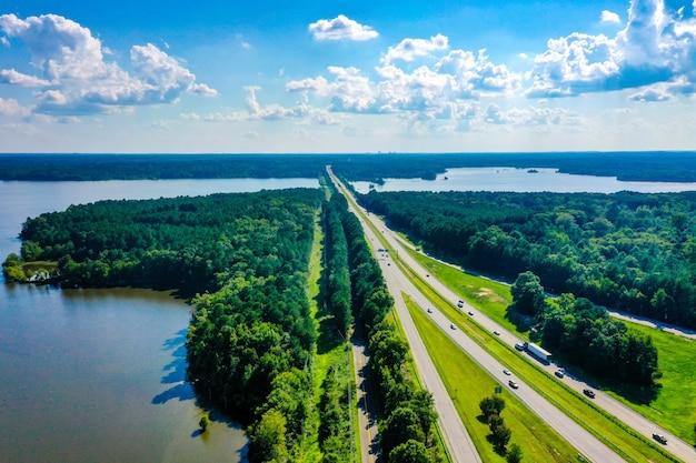 Luchtfoto van falls lake in north carolina en interstate snelweg met een bewolkte blauwe hemel