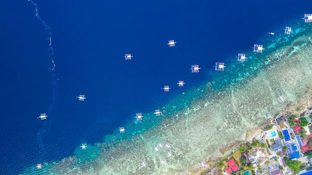 Luchtfoto van filipijnse boten die bovenop heldere blauwe wateren drijven