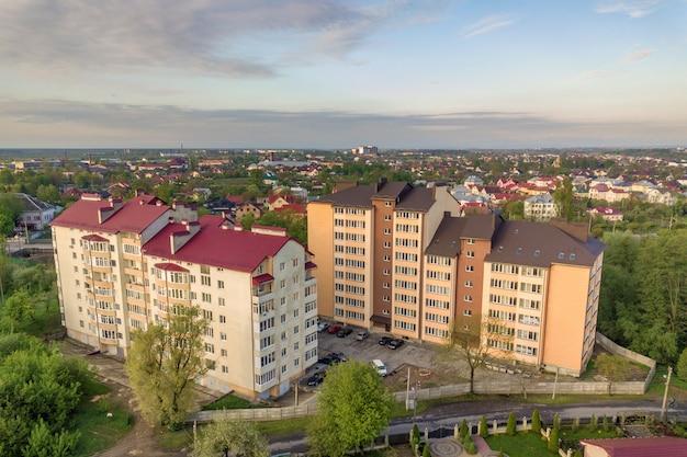 Luchtfoto van flatgebouwen met meerdere verdiepingen in groene woonwijk.