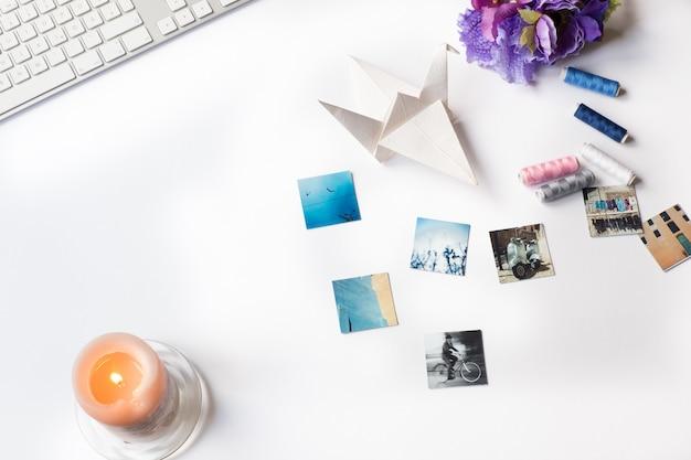 Luchtfoto van foto's, een dun toetsenbord, een oranje kaars, papieren origami en draad op een wit bureau