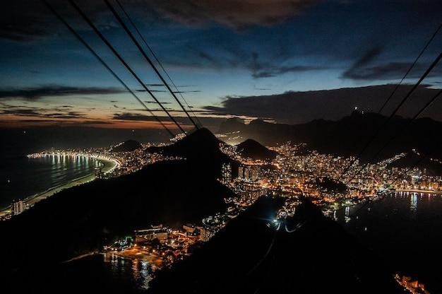 Luchtfoto van gebouwen van de stad lichten 's nachts in de buurt van de zee en de bergen