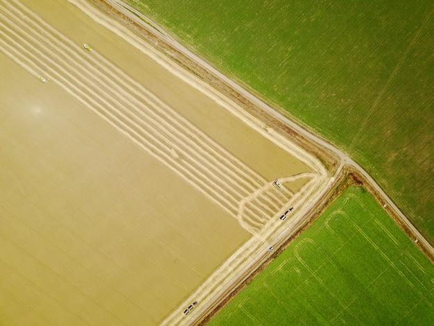 Luchtfoto van gele oogstmachines bezig met tarweveld.