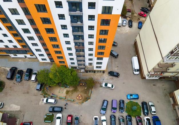 Luchtfoto van geparkeerde auto's op parkeerplaats tussen hoge flatgebouwen.