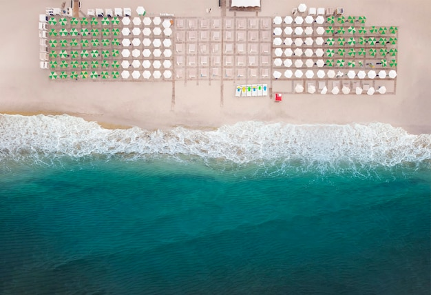 Luchtfoto van geweldig strand met parasols en turquoise zee in warme zomerseizoen.