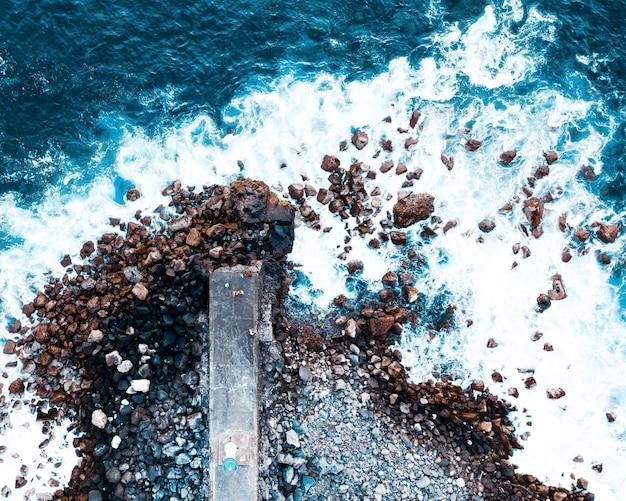 Luchtfoto van golven die op rotsen beuken