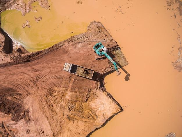 Luchtfoto van graafmachine en vrachtwagen werken