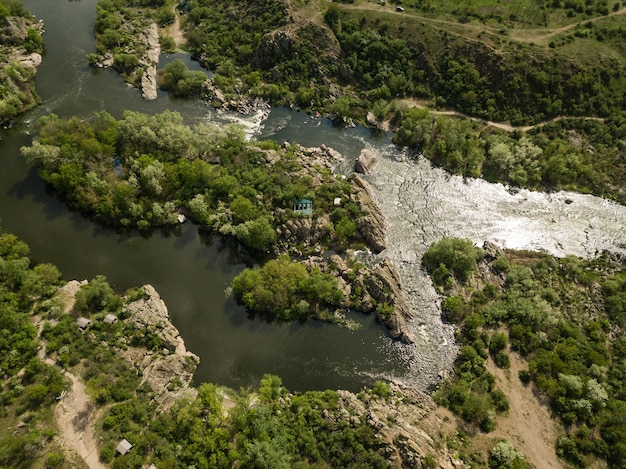 Luchtfoto van granietbergen en stroomversnellingen op de southern bug-rivier, omgeven door bomen en grassen, het dorp mihiia. oekraïne. beroemde plek om te raften en kajakken