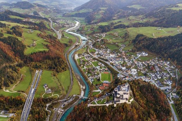 Luchtfoto van groene weiden met dorpen en bossen in de bergen van oostenrijkse alpen.