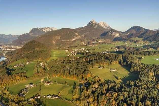 Luchtfoto van groene weiden met dorpen en bossen in de oostenrijkse bergen van de alpen.