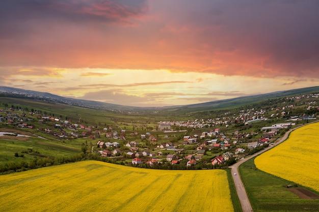 Luchtfoto van grond weg met bewegende auto's in groene velden met bloeiende koolzaad planten, voorstad huizen op horizon en blauwe hemel kopie ruimte achtergrond. drone fotografie.