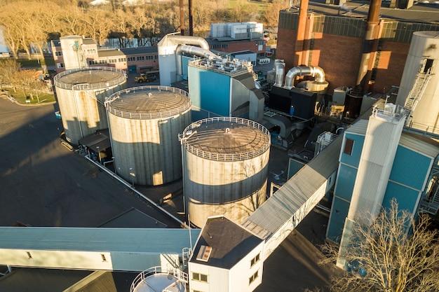Luchtfoto van grote brandstofreservoirs in de aardolie-industriezone en metalen uitlaatpijpen van de olieraffinaderijfabriek.
