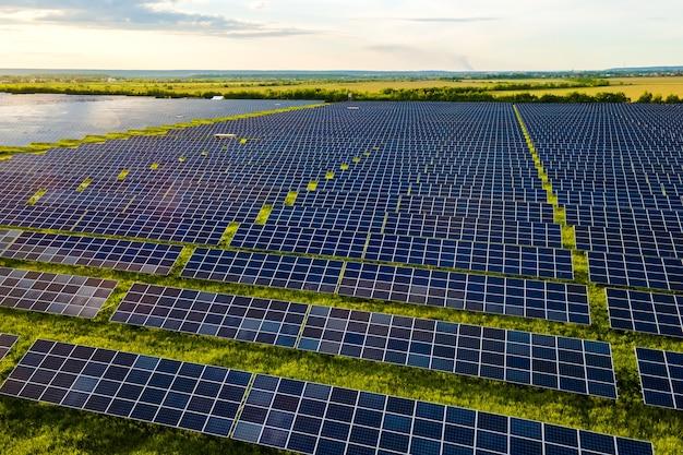 Luchtfoto van grote duurzame elektrische centrale met veel rijen fotovoltaïsche zonnepanelen voor het produceren van schone ecologische elektrische energie. hernieuwbare elektriciteit met nul-emissieconcept.