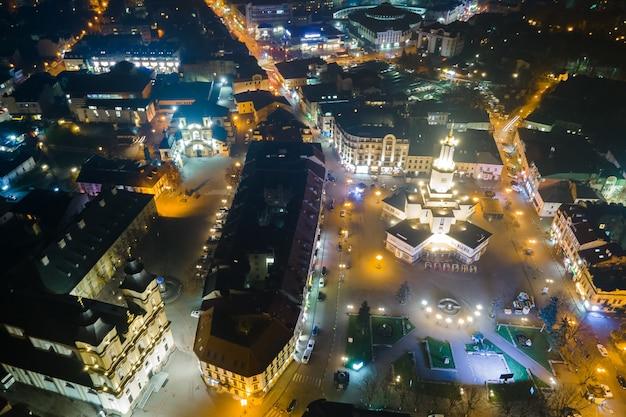 Luchtfoto van helder verlichte straten en gebouwen in het centrum van de oekraïense ivano-frankivsk 's nachts.