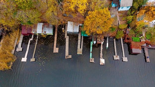 Luchtfoto van herfst landschap van dorp aan de oevers van de rivier met loopbruggen voor boten