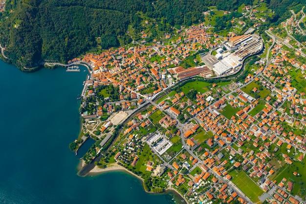 Luchtfoto van het comomeer, dongo, italië. kustlijn wordt gewassen door blauw turkoois water