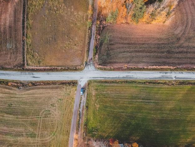 Luchtfoto van het kruispunt van twee wegen omringd door velden. foto genomen vanaf een drone. finland, pornainen.