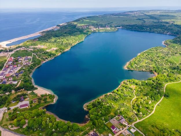 Luchtfoto van het meer aan de zeekust en het bos gemaakt met drone aan de baltische zee, yantarny, rusland