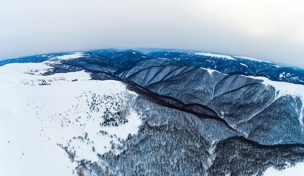 Luchtfoto van het mystieke landschap van een winterbergbos op een bewolkte ijzige dag