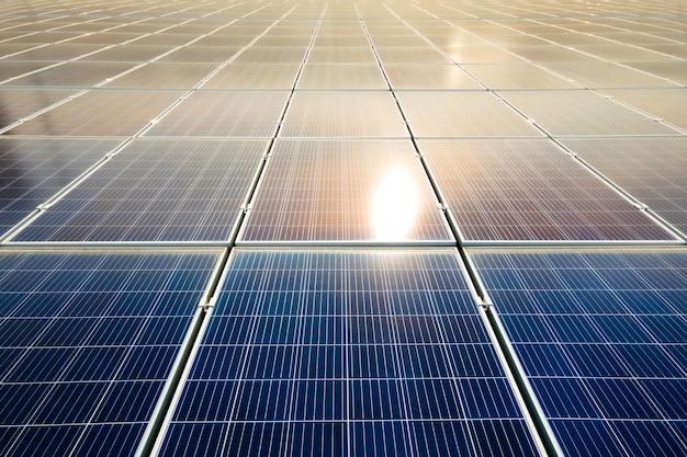 Luchtfoto van het oppervlak van blauwe fotovoltaïsche zonnepanelen gemonteerd op het dak van een gebouw voor het produceren van schone ecologische elektriciteit. productie van hernieuwbare energieconcept.