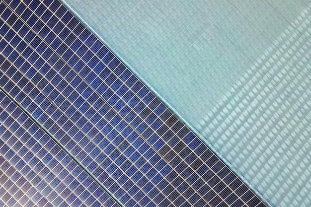 Luchtfoto van het oppervlak van blauwe fotovoltaïsche zonnepanelen gemonteerd op het dak van het gebouw voor het produceren van schone ecologische elektriciteit productie van hernieuwbare energieconcept