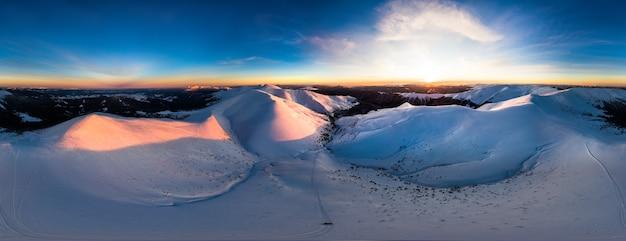 Luchtfoto van het overweldigende winterpanorama van de besneeuwde hellingen en heuvels