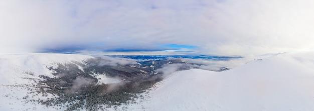 Luchtfoto van het prachtige winterpanorama van de besneeuwde hellingen en heuvels tussen de weelderige witte wolken