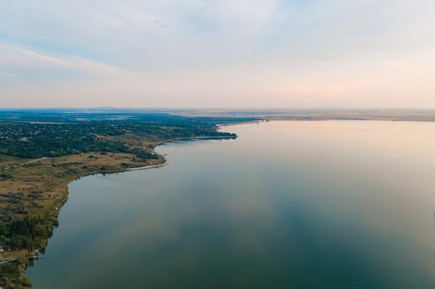 Luchtfoto van het schilderachtige landschap van land, bomen, lucht weerspiegeld in het water.