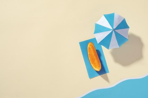 Luchtfoto van het strand met paraplu en sinaasappelschijfje op een handdoek op het zand