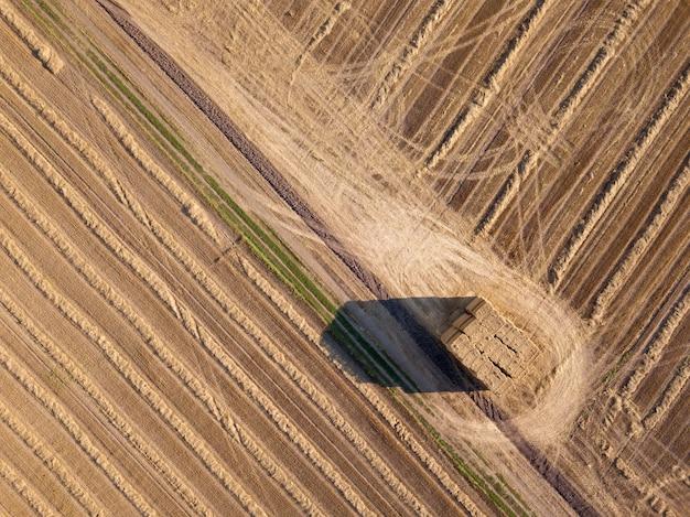 Luchtfoto van het veld na de oogst. stapels stro op een landbouwgebied. ecologische biobrandstof en kunstmest voor werk in het veld.