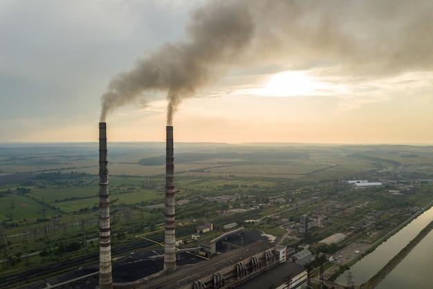 Luchtfoto van hoge schoorsteen pijpen met grijze rook uit kolencentrale. productie van elektriciteit met fossiele brandstof.
