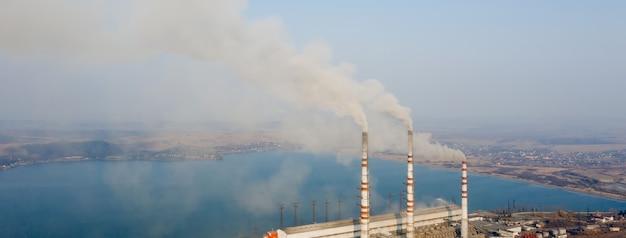 Luchtfoto van hoge schoorsteenpijpen met grijze rook van kolencentrale. opwekking van elektriciteit met fossiele brandstof.
