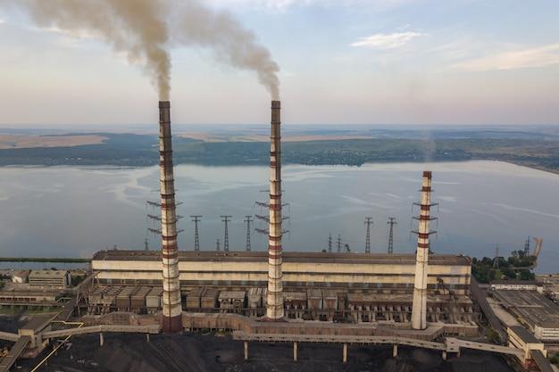 Luchtfoto van hoge schoorsteenpijpen met grijze rook van kolencentrale. productie van elektriciteit met fossiele brandstof.