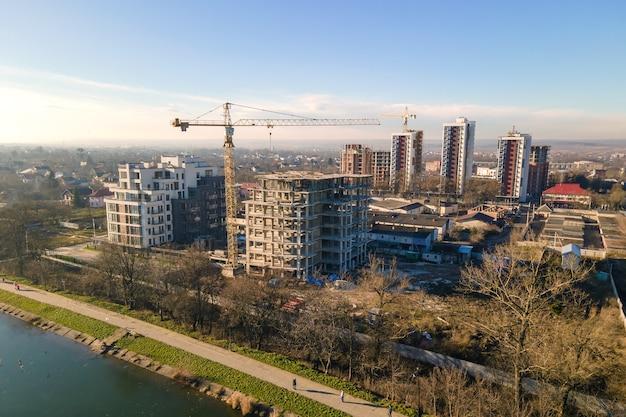 Luchtfoto van hoge torenkraan en residentiële appartementsgebouwen in aanbouw. vastgoed ontwikkeling.