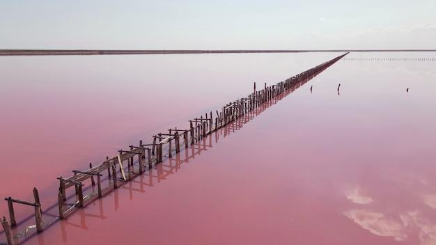 Luchtfoto van houten constructies voor het verzamelen van zout op een roze meer