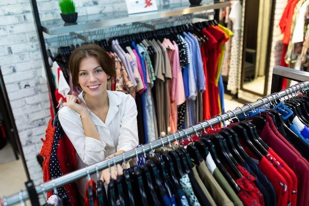 Luchtfoto van jonge aantrekkelijke vrouw permanent door luiaards staan op kleding winkel