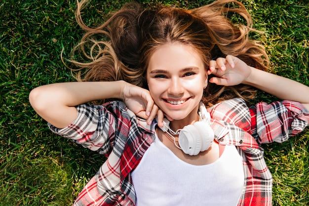 Luchtfoto van kaukasisch debonair meisje dat van het leven geniet. positieve blanke vrouw in grote koptelefoon liggend op groen gras.