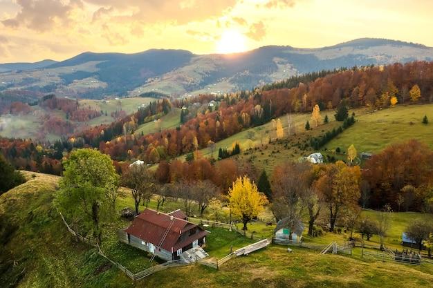 Luchtfoto van kleine herdershuizen op brede weide tussen herfstbos in de oekraïense karpaten bij zonsondergang.