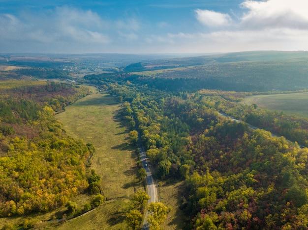 Luchtfoto van kleurrijke bos in de herfst met weg doorsnijden
