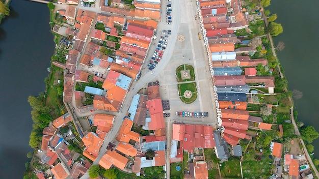 Luchtfoto van kleurrijke gebouwen met rode pannendaken op het middeleeuwse plein en het oude kasteel in telc, tsjechië